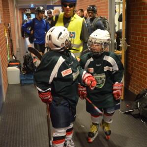 Smålirarna på väg in till det pågående hockeylägret gör stora ögon när de ser de större killarna!