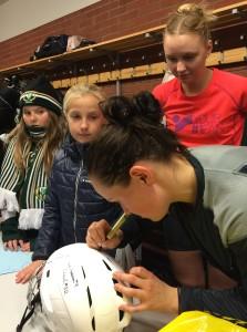 Målskytten Daniella Carlsson skriver sin autograf på en ung beundrarinnas hjälm. Karin Åström övervakar i väntan på sin tur Foto: Marie Angle/fbkbloggen
